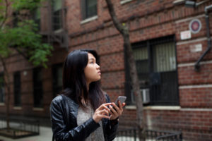 Girl with leather jacket explores the city using her phone for instructions