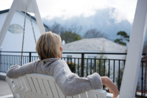 Woman sitting on swing terrace, looking at view