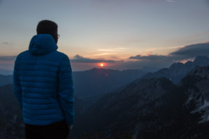 Hiker stands on the top of the mountain, watching a sunrise