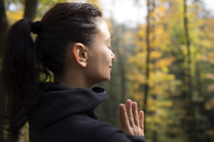 Woman standing in the woods with hands together, meditation