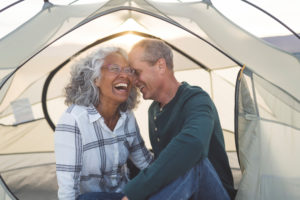 A man whispered to his laughing wife in a comfortable tent.