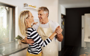 Middle-aged couple dancing in their kitchen.