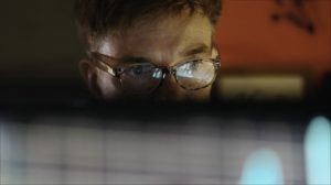 A man looks at a computer screen, which reflects on his glasses