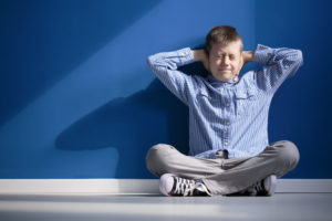A young boy in a blue shirt sits against a blue wall, covering his ears with both hands.