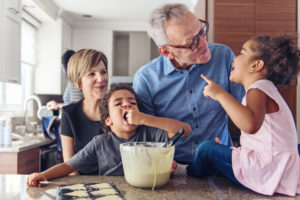 Two grandparents teach children how to make cupcakes (while a child tastes the batter!).