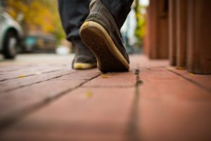 View of man's shoes while walking on a sidewalk