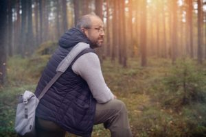 Man sits in the forest with thoughtful expression on his face