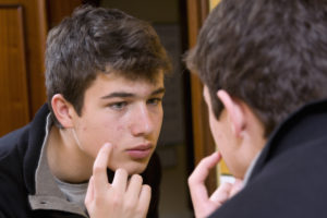 Teen examines acne in the mirror
