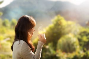 Woman standing outside looking at thoughtful while holding a cup of coffee.