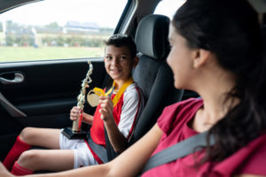 Boy showing his mommy football the trophy won in the summer camp