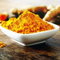 Bowl of turmeric powder with roots in the background