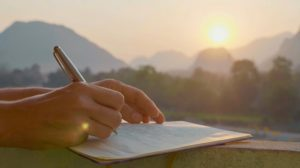 Close up of hand writing in a magazine in a beautiful outdoor environment at sunrise