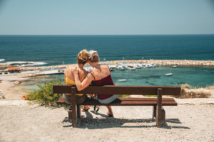 Female couple on the bench admiring the sea