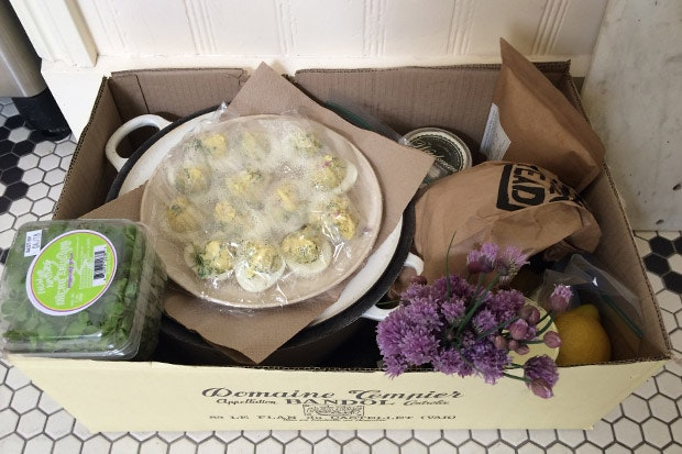 A box with a platter full of eggs, flowers and green salad.