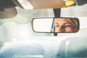 A woman's eyes reflected in her mirror as they drove