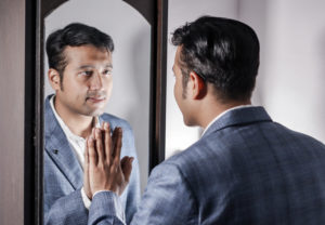 A man in a suit looks at his reflection while touching the mirror.