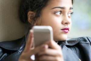 The girl grows sad after reading a message from a cyberbully.