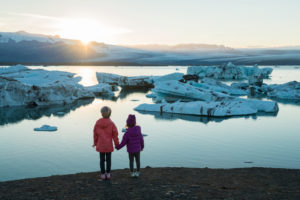 The sisters hold hands and watch a melting glacier.