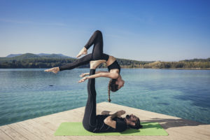 Couple practicing acroyoga in nature on beautiful lake