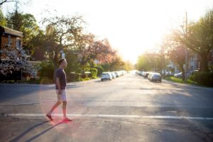 Man walking on the street in a quiet neighborhood at sunset