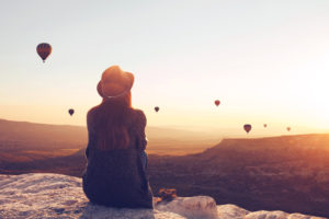 A young woman sits and sees hot air balloons crossing the horizon.