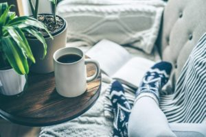 View of one's feet in warm socks with a book and coffee on a sofa