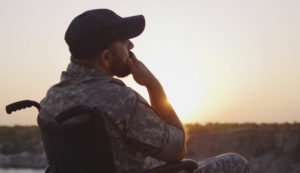 Military veteran sits in wheelchair, watching a sunset