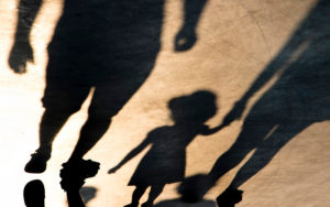 Shadows of the parents holding the child's hand